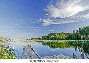 Lago tranquilo bajo el cielo vívido en verano