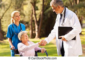 Médico saludando con pacientes mayores