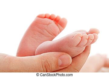 Madre sosteniendo pies recién nacidos