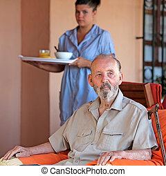 Mayor con cuidadora o enfermera trayendo comida