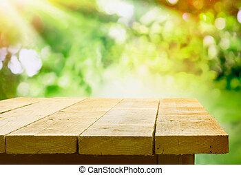 Mesa de madera vacía con bokeh jardín