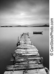 Mirando un muelle desolado y un barco, blanco y negro