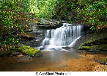 Moción borrosa cascadas naturaleza pacífica paisaje en montañas de cresta azul con árboles verdes exuberantes, rocas y agua que fluyen
