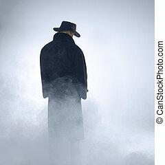 Mujer con abrigo de trinchera y parada en la niebla