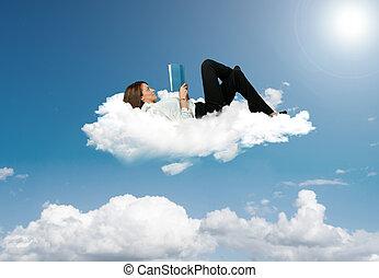 Mujer de negocios leyendo un libro en una nube