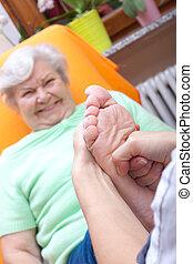 Mujer enfermera masajeando pies de un paciente