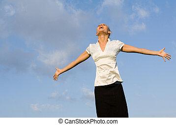 Mujer feliz cantando al aire libre, mirando los brazos hacia afuera