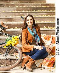 Mujer feliz con bicicleta en el parque de otoño