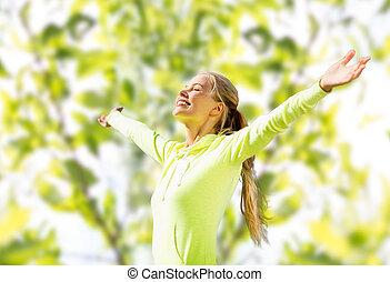 Mujer feliz con ropa deportiva levantando la mano