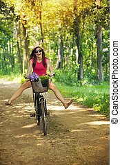 Mujer feliz disfrutando de un paseo en bicicleta en el bosque