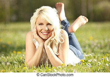 Mujer feliz tirada en un prado