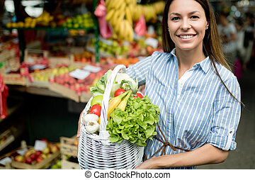 Mujer joven comprando verduras