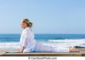 Mujer madura en posición de yoga para perros