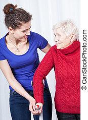 Mujer madura practicando caminar con enfermera