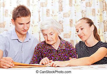 Mujer mayor con dos nietos sonrientes