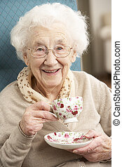 Mujer mayor disfrutando de una taza de té en casa