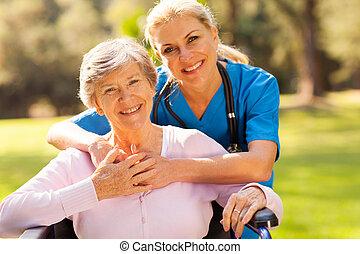 Mujer mayor en silla de ruedas al aire libre con cuidador