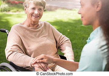Mujer mayor y enfermera cariñosa