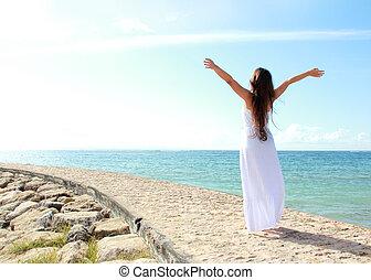 Mujer relajada en la playa con brazos abiertos disfrutando de su libertad