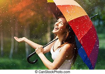 Mujer sonriente con paraguas buscando lluvia