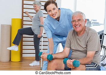 Mujer terapeuta que ayuda a un hombre mayor con pesas