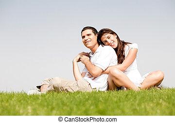 Mujeres jóvenes felices con brazos alrededor de su marido y tumbadas sobre su hombro en un parque
