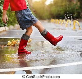 Niño con botas de lluvia roja saltando en un charco