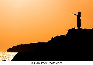 Niño con brazos levantados de alegría en el atardecer de las vacaciones