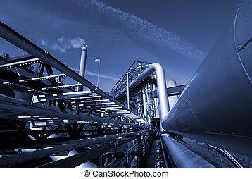 Oleoductos industriales en tuberías contra el cielo en tono azul
