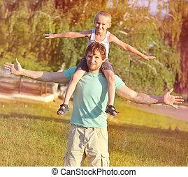Padre y Hijo de la Familia sentados sobre los hombros jugando a la Felicidad con la naturaleza del verano en el fondo