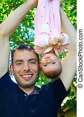 Papá sostiene al bebé al revés al aire libre.