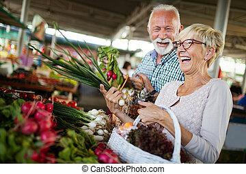 Pareja sonriente con cestas de verduras en el mercado