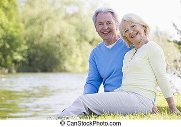 Parejas al aire libre en el parque junto al lago sonriendo