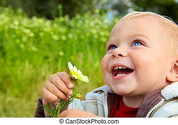 Pequeño bebé riéndose con margarita