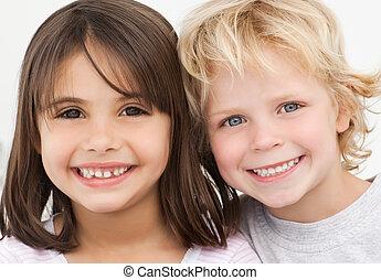 Retrato de dos niños felices en la cocina