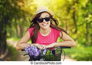 Retrato de mujer sonriente en bicicleta en el parque