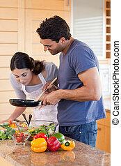 Retrato de una joven pareja cocinando con una sartén