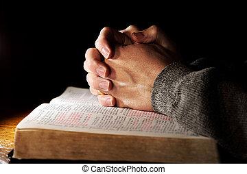 Rezando manos sobre una biblia sagrada