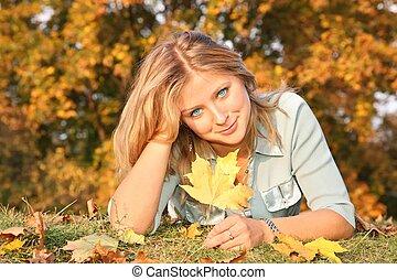 Rubia de ojos azules con la hoja amarilla en la hierba