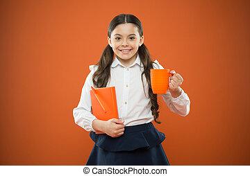 Toda la felicidad depende de un desayuno escolar. Una niña pequeña disfrutando de sus vacaciones en la escuela de origen naranja. Una niña linda sonriendo con un libro de notas. Una colegiala feliz tomando una bebida caliente en la escuela