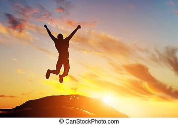 Un hombre feliz saltando de alegría en la cima de la montaña al atardecer. Éxito