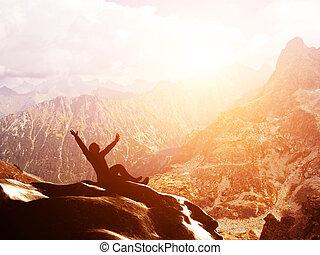 Un hombre feliz sentado en la cima de una montaña con las manos levantadas al atardecer