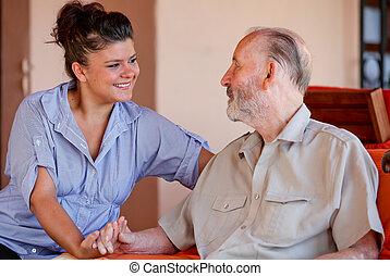 Un hombre mayor con cuidadora o nieta.