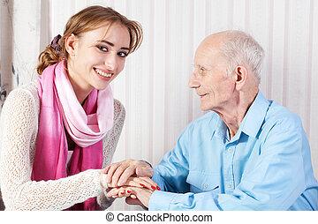 Un hombre mayor con su cuidador en casa