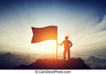 Un hombre orgulloso levantando una bandera en el pico de la montaña. Desafío, logro