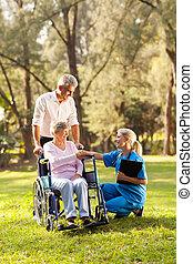 Un médico en silla de ruedas saludando a una paciente mayor