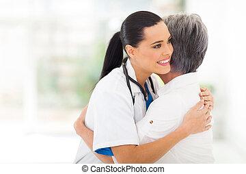 Un médico joven abrazando a un paciente mayor