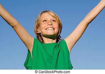 Un niño feliz y sonriente con brazos levantados de felicidad