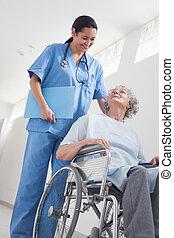 Un paciente mayor en silla de ruedas junto a una enfermera