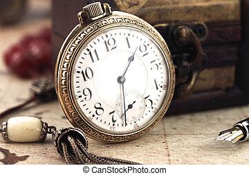 Un reloj de bolsillo antiguo y objetos de decoración